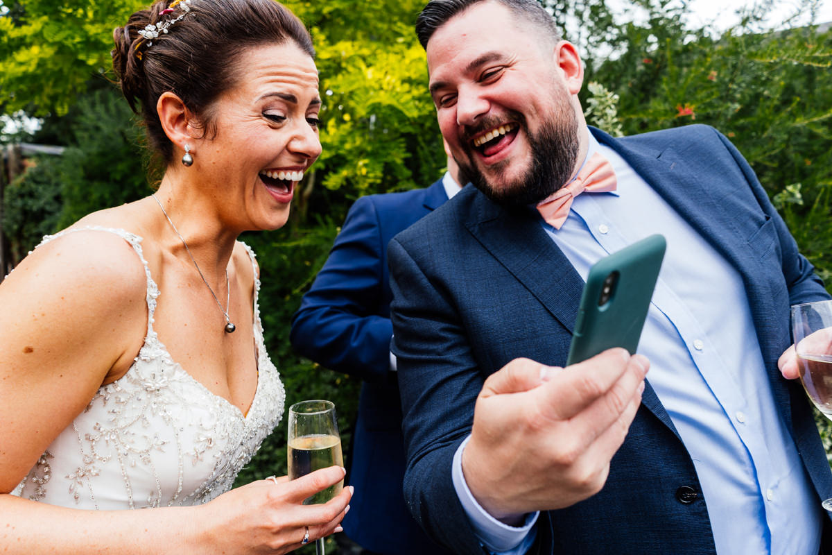 bride and brother laughing at something on the phone