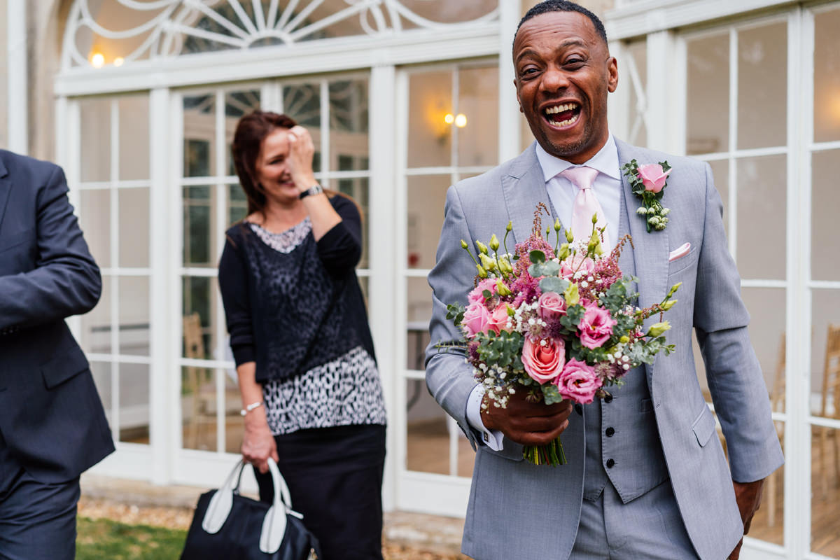 best man laughing with bouquet