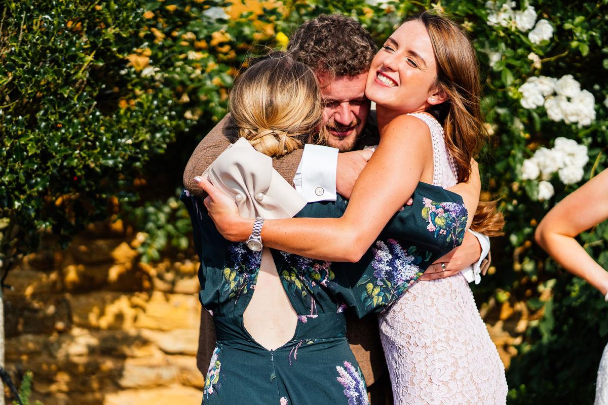 big hugs during drinks reception at wedding