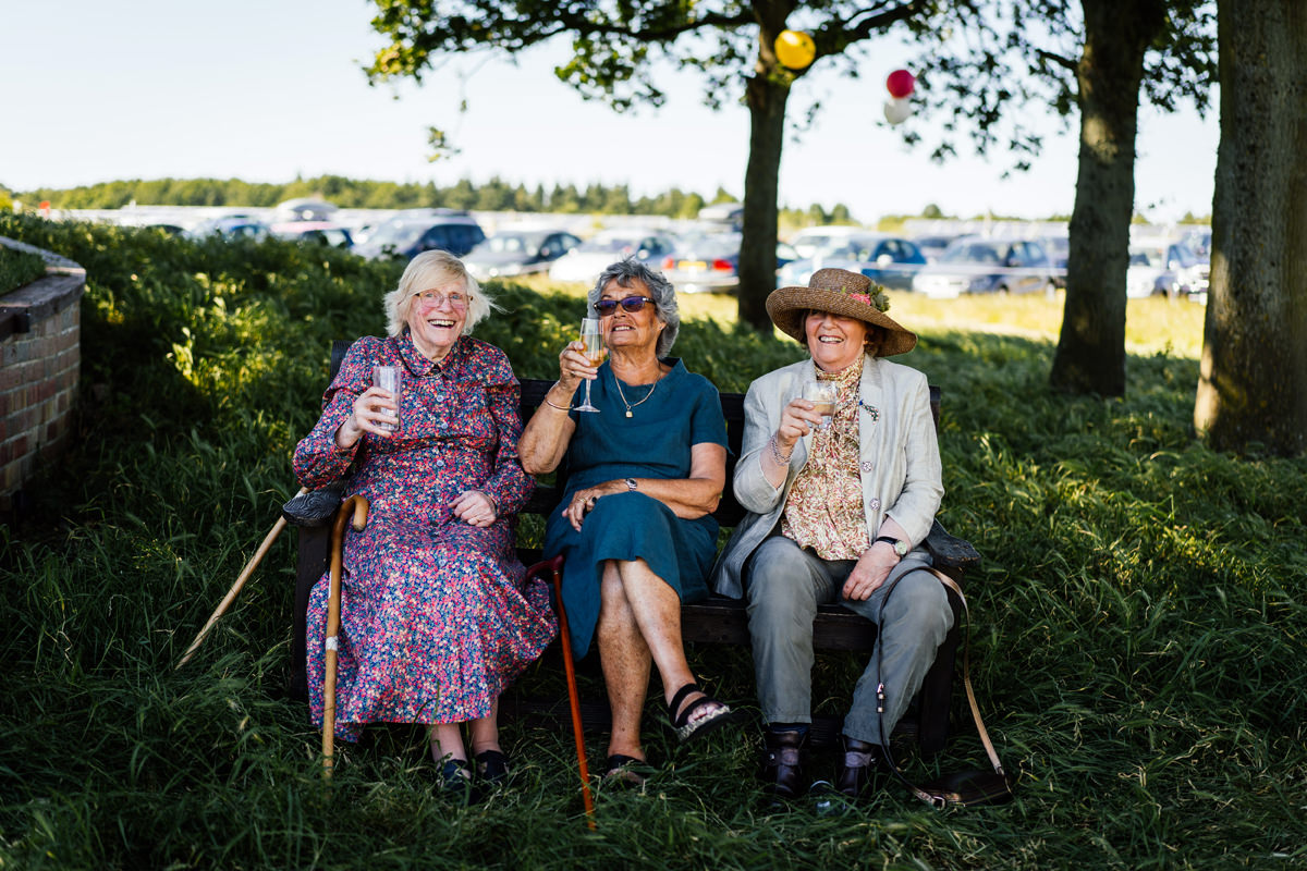 three ladies chilling in the shade on a hot summers wedding day