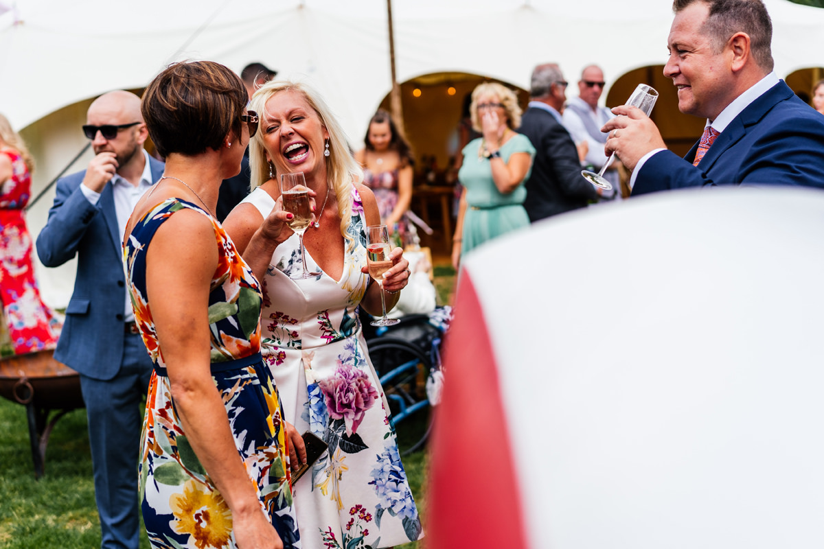 candid moment of guests laughing during drinks reception