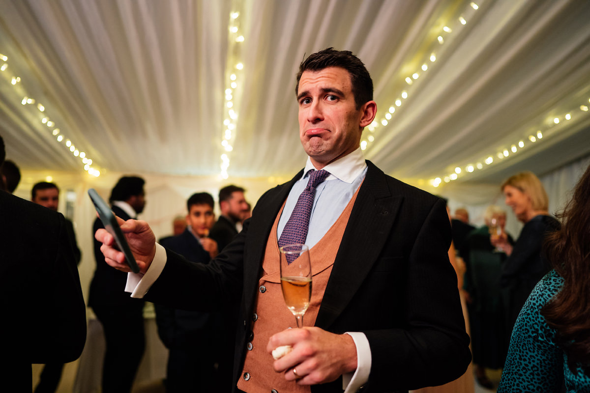 wedding guest pulling funny face when caught on camera