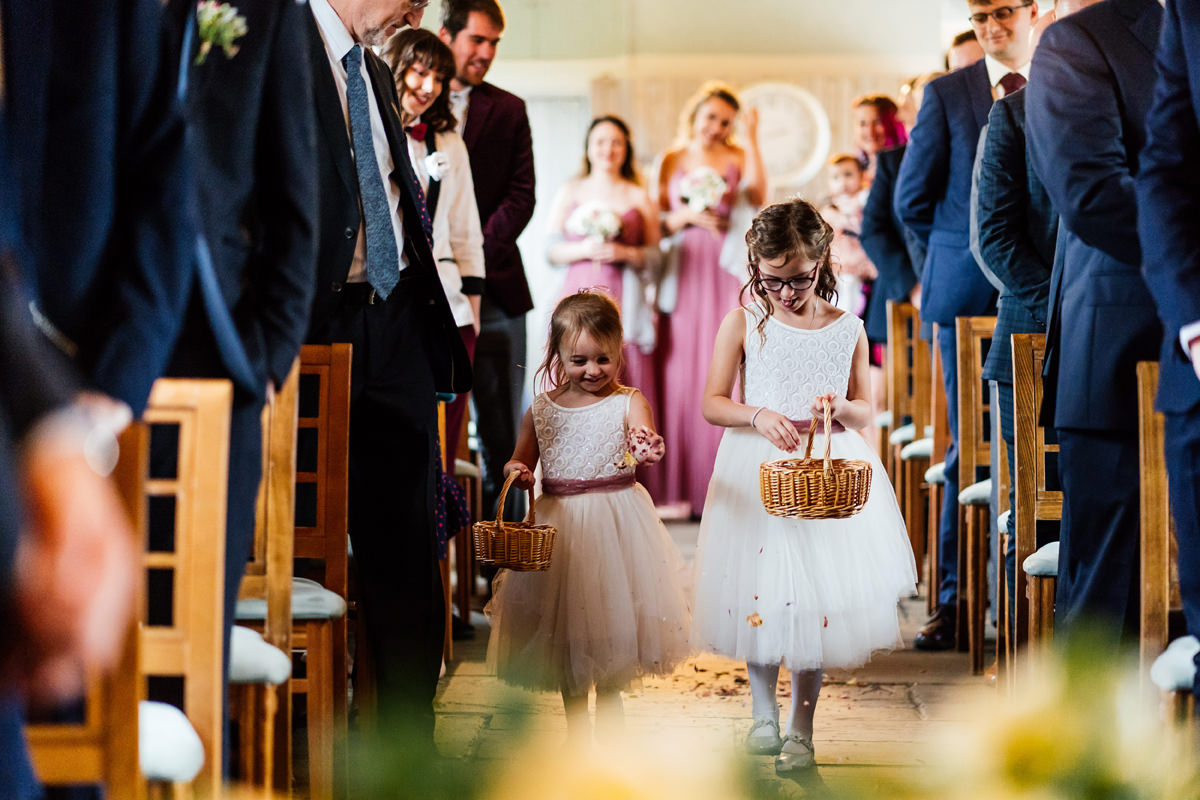 flower girls walking down the aisle at the start of the ceremony