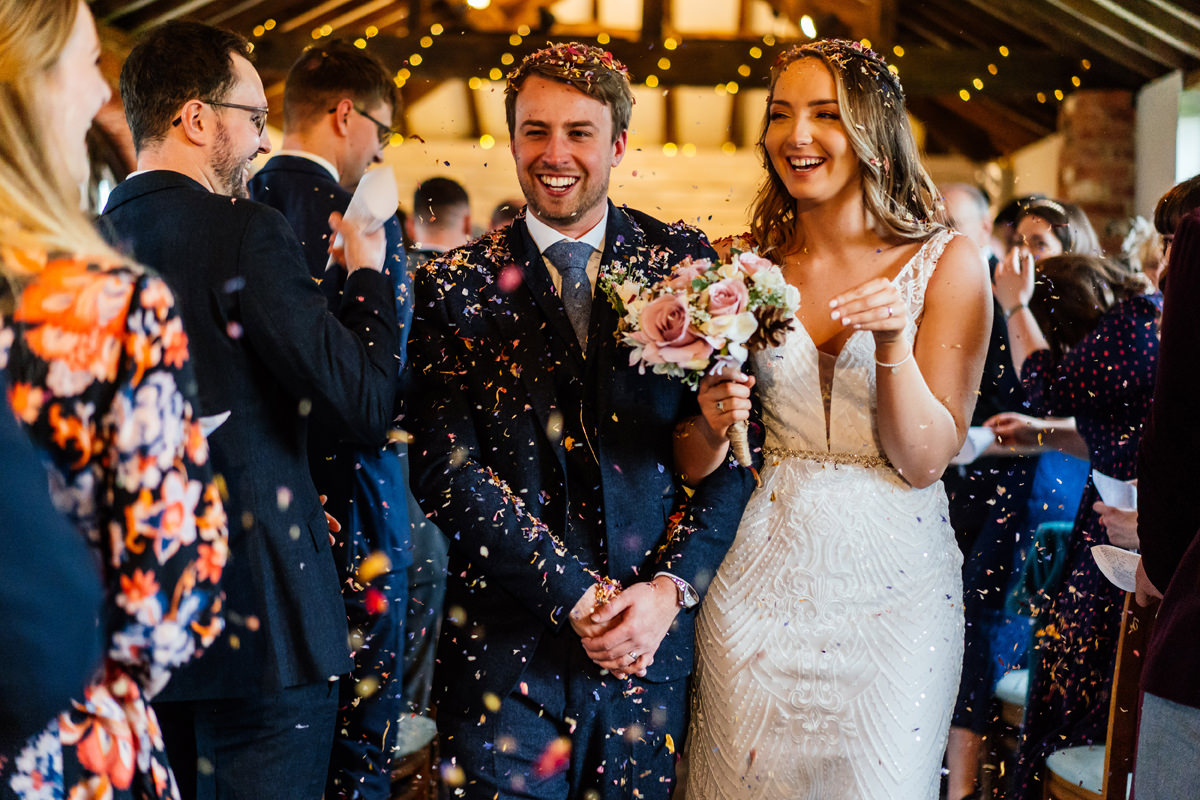 bride and groom walk back down the aisle showered with confetti