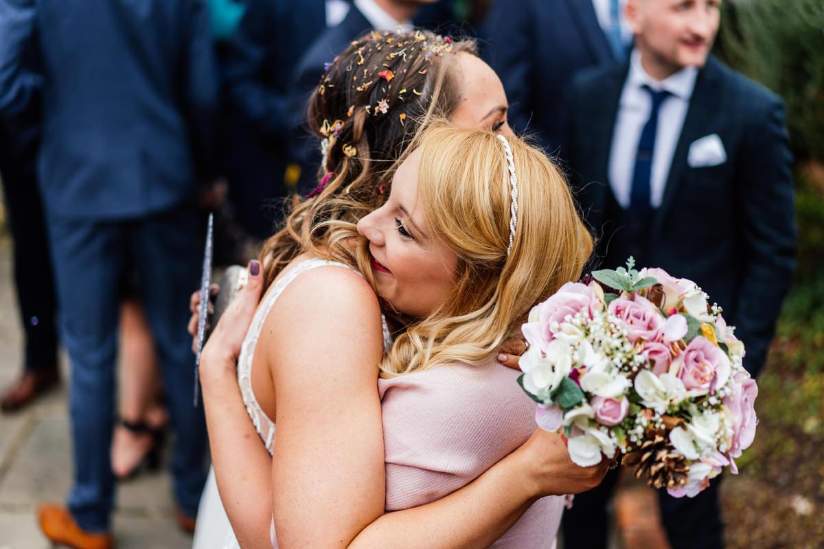 friend gives the bride a hug