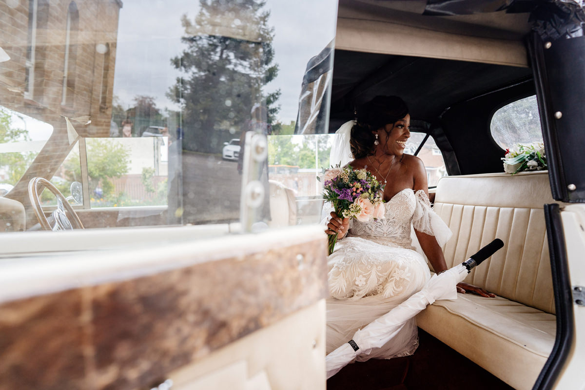 bride sitting in the wedding car waiting for her bridesmaids