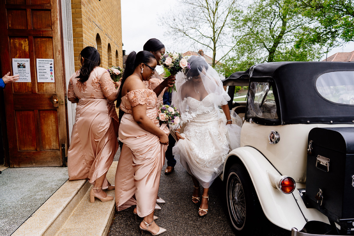 bride helped out of the wedding car by her bridesmaids