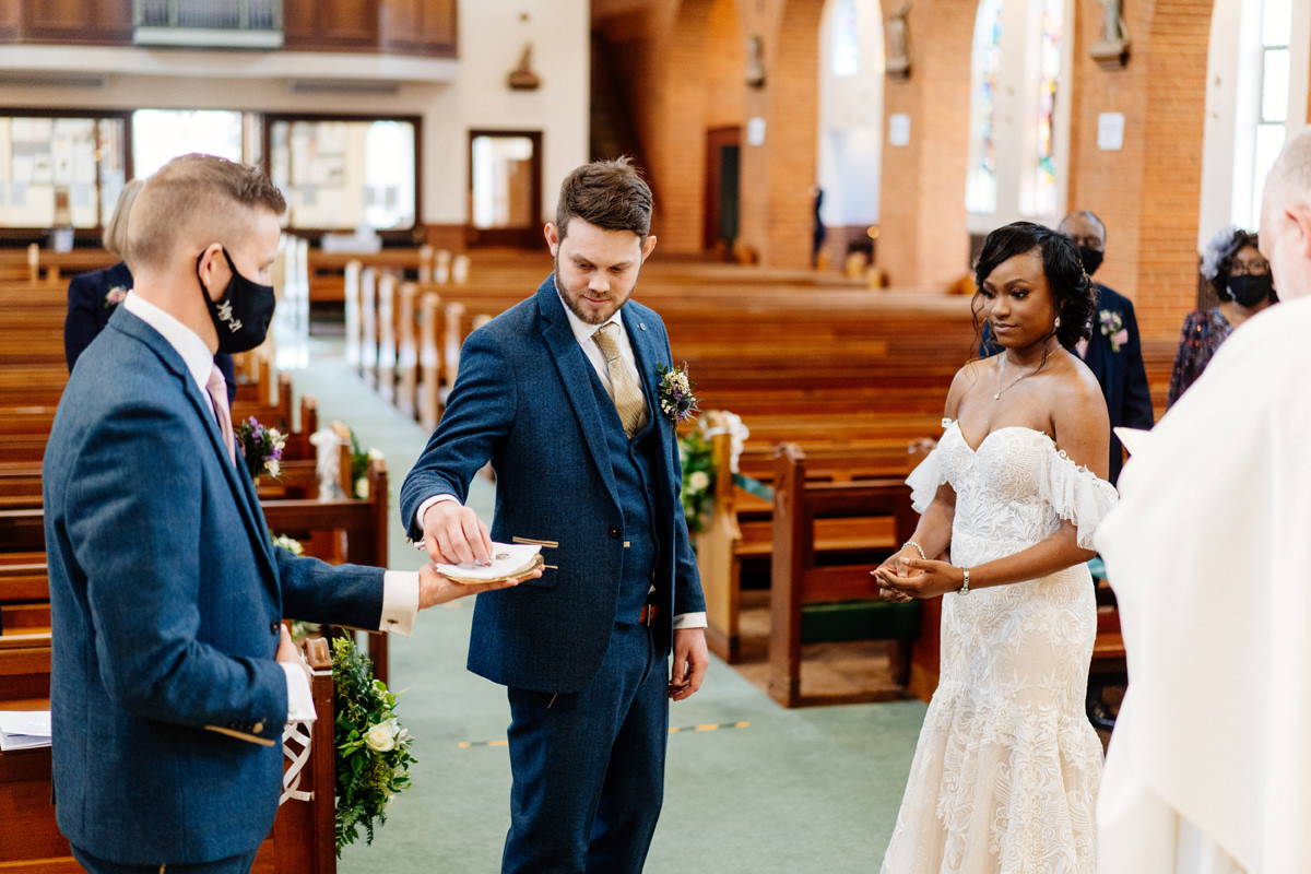 groom taking the brides wedding ring from best man