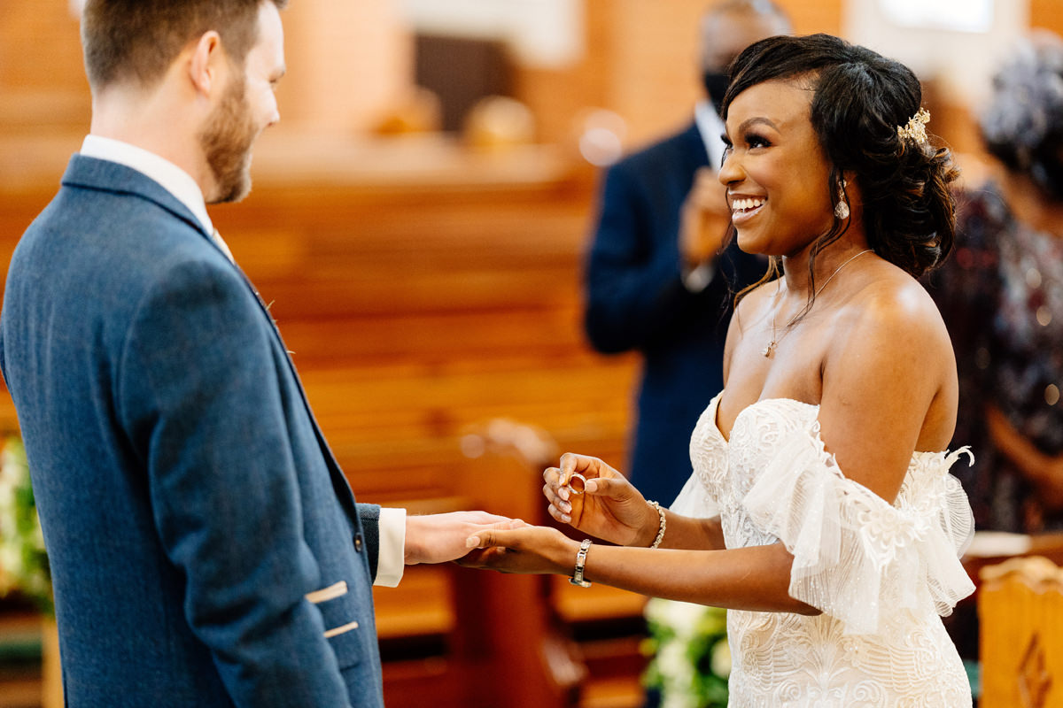 bride giving her groom his wedding ring