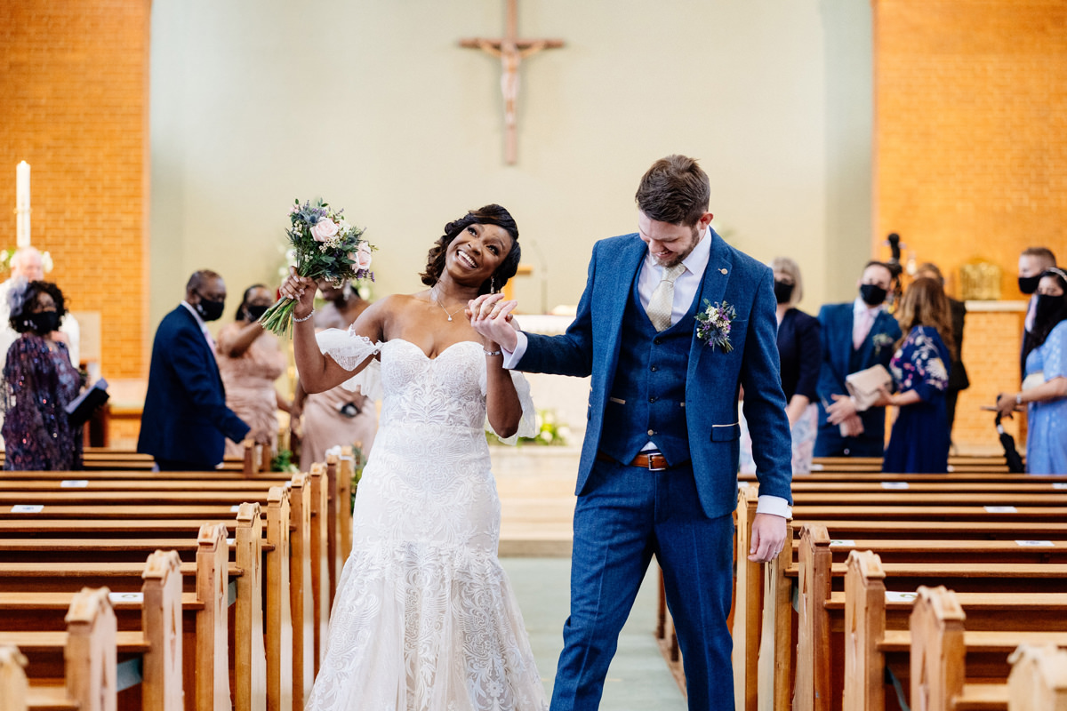 bride and groom dance down the aisle to exit church