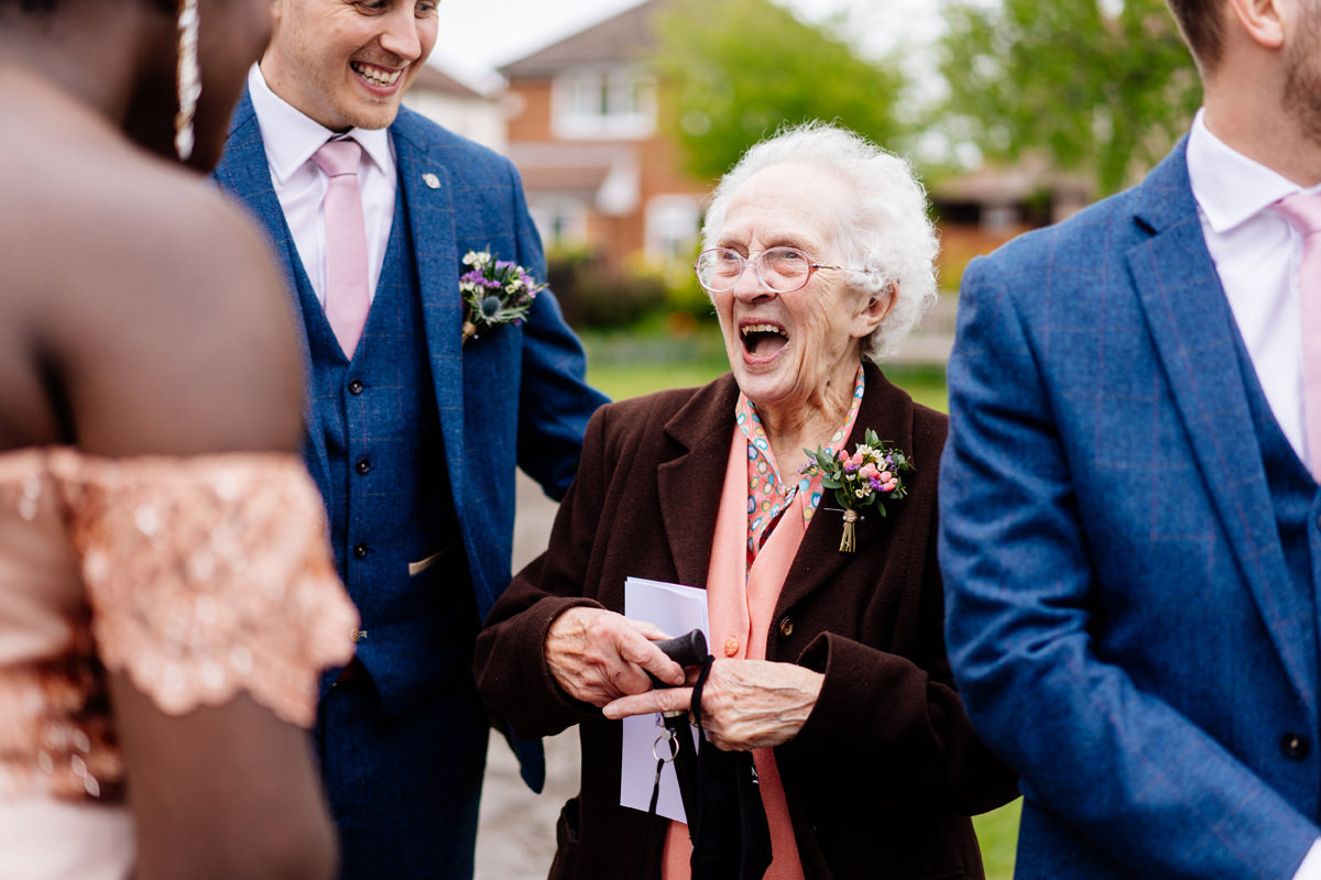 groom's grandmother laughing outside the church