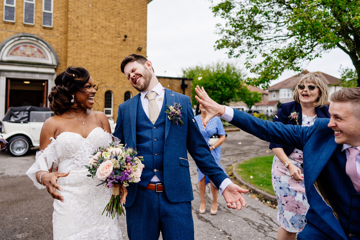 brother of groom throws confetti in groom's face