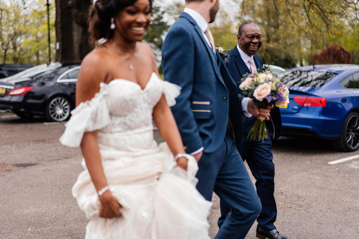 Father of the bride smiling as bride and groom walk