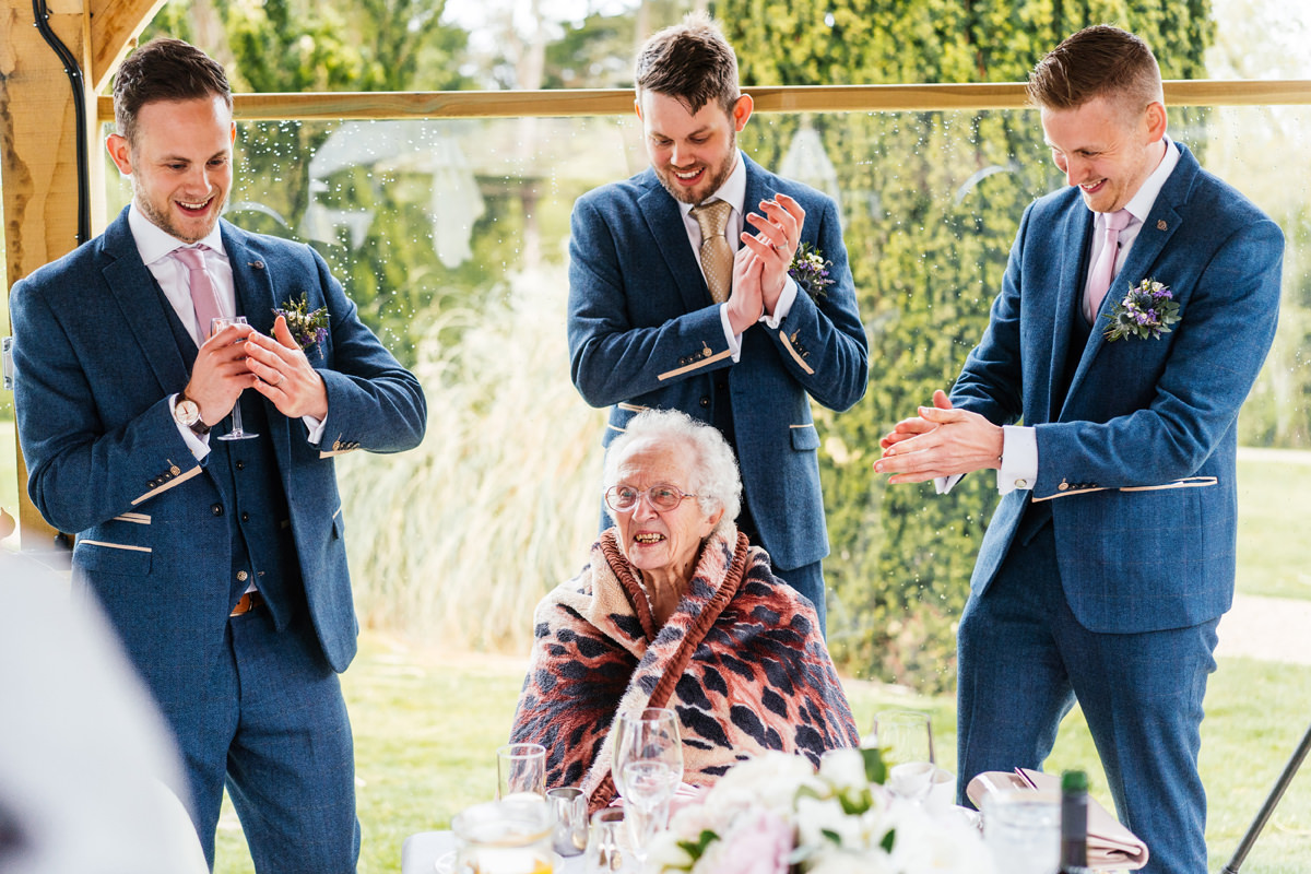 groom and his brothers sing happy birthday to their grandmother