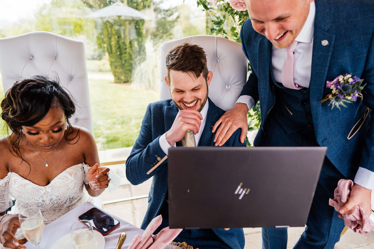 wedding guests connect with family over zoom call on laptop