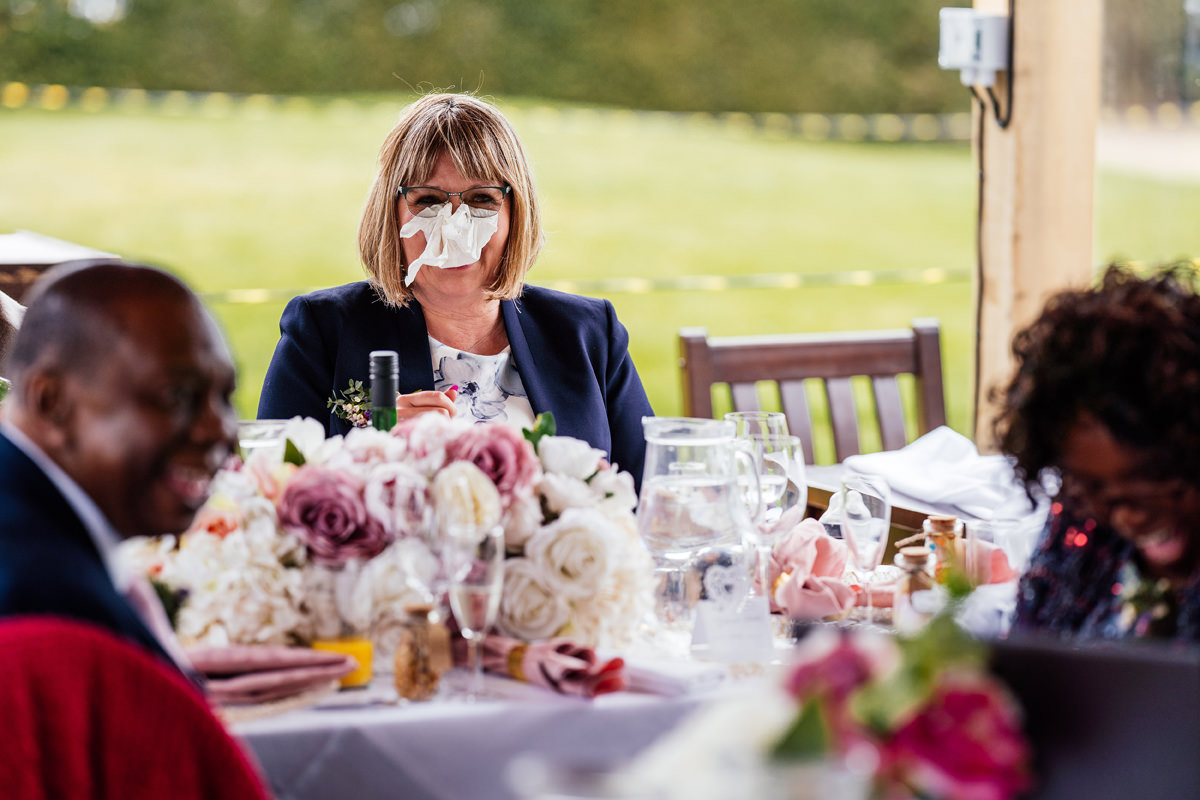 mother of groom being silly with napkin over her face