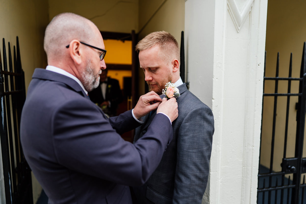 Groom having his button hole put on