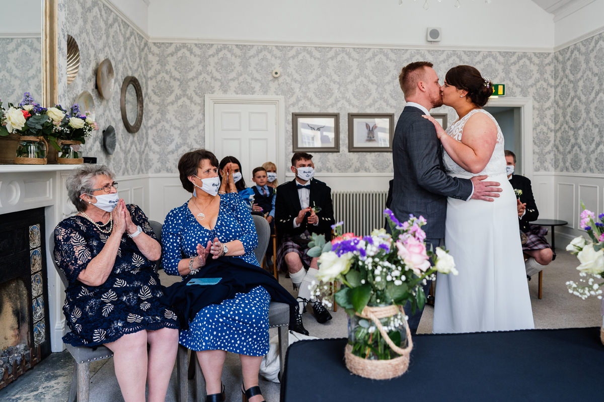 bride and groom have a first kiss