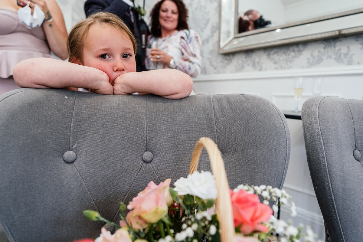 flower girls watches on as bride and groom cut cake