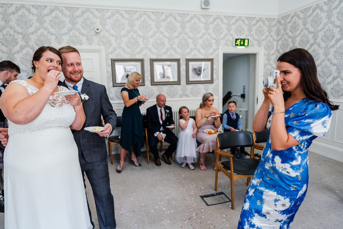 guest takes a Polaroid picture of the bride and groom