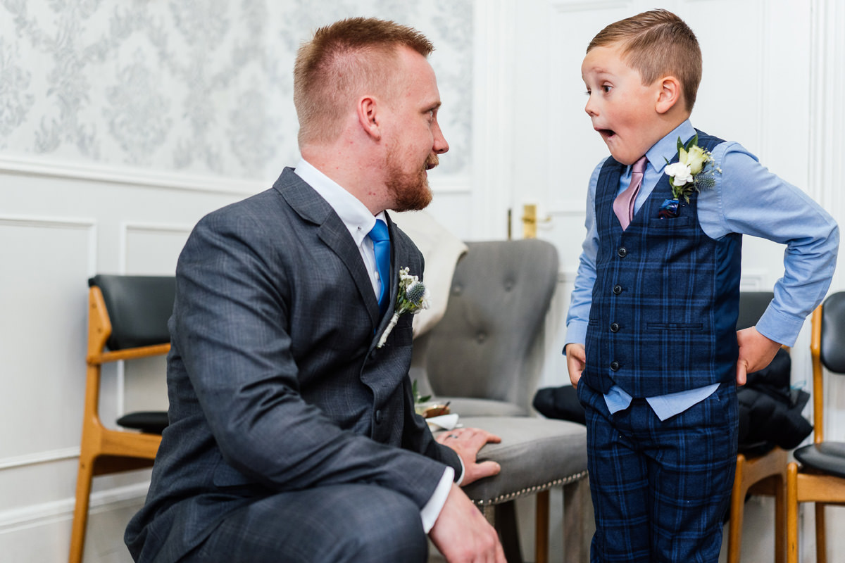 groom and ring bearer having a laugh