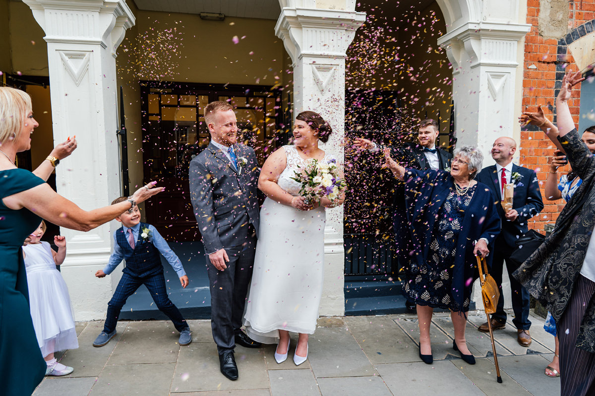 bride and groom showered with confetti